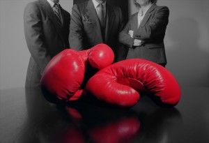 Three business people stand behind a conference table with red boxing gloves on it. The photograph is black & white except for the boxing gloves which are left red for emphasis.